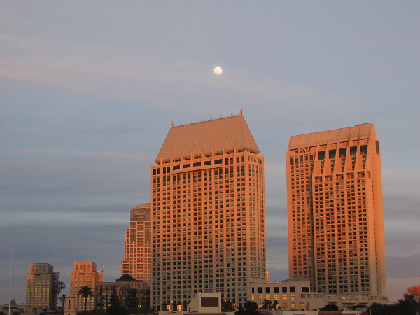 The Manchester Grand Hyatt towers turn golden in the last rays of the sun. A nearly full moon rises above them.