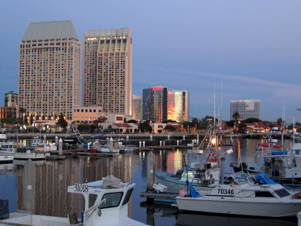 Sunset's bright red and yellow reflects from the silvery Marriott Marquis, and onto the calm water of Tuna Harbor.