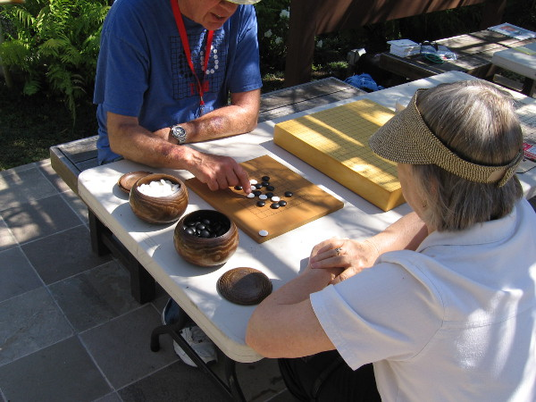 Some attending the Cherry Blossom Festival try their hand at the ancient game of Go.