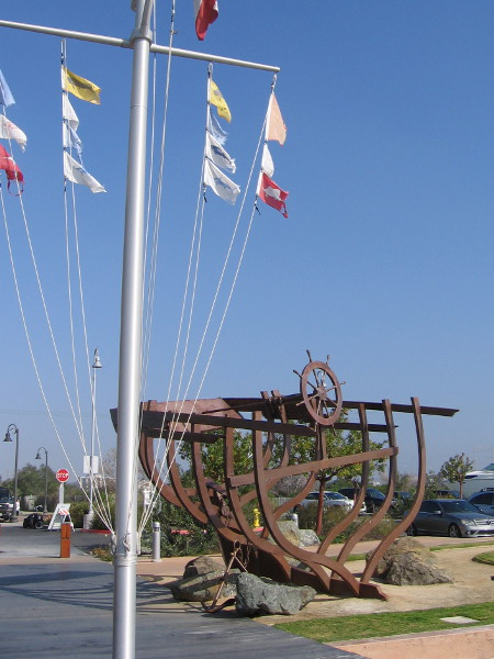 This huge metal sculpture by the marina flags is called Le Bateau Ivre, by artist Alber De Matteis, 2008.