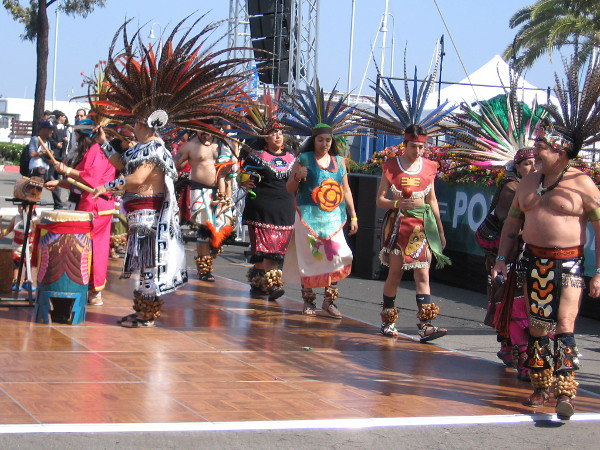 The Azteca Dancers file onto the stage to the beat of drums.