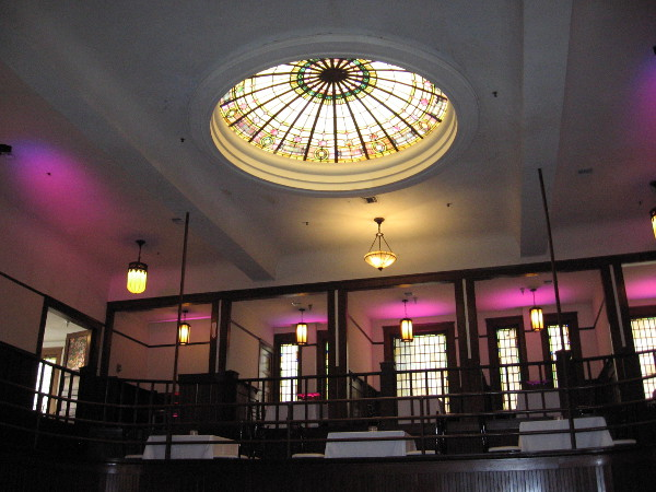 This gorgeous stained glass skylight and purple floor lights tinting the walls make a memorable dining experience at these tables on the second floor of The Abbey.