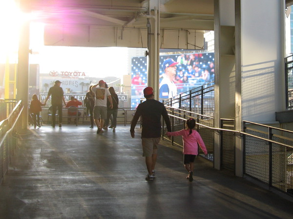 It's approaching game time. Fans walk up a ramp to the upper level.