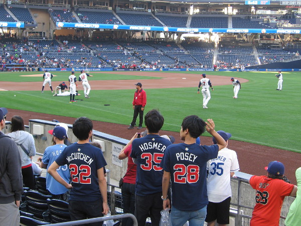 Fans of Team USA watch their baseball heroes warm up on the field before the game.