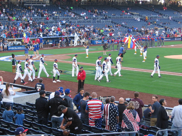 Players for Team USA come out of the dugout for the opening ceremony.