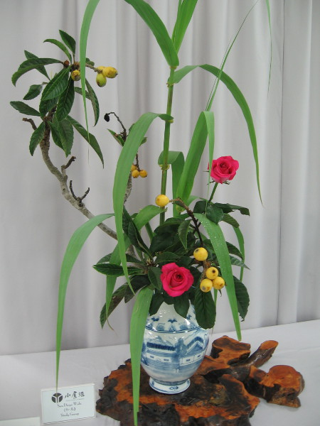 A spectacular arrangement by ikebana Grandmaster Akiko Bourland. Materials include loquat, rose, rush.