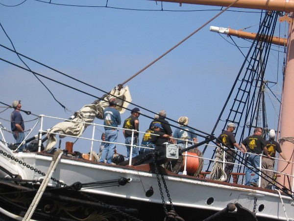 Volunteers and employees of the Maritime Museum of San Diego watch from the deck below.