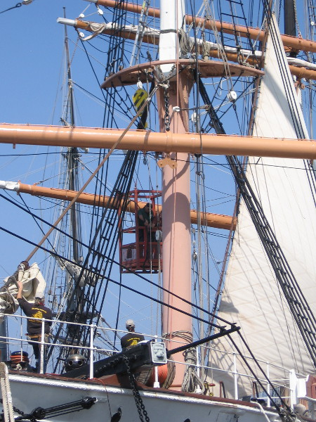 The bottom end of the cable was attached, now back up to the top of the foremast...