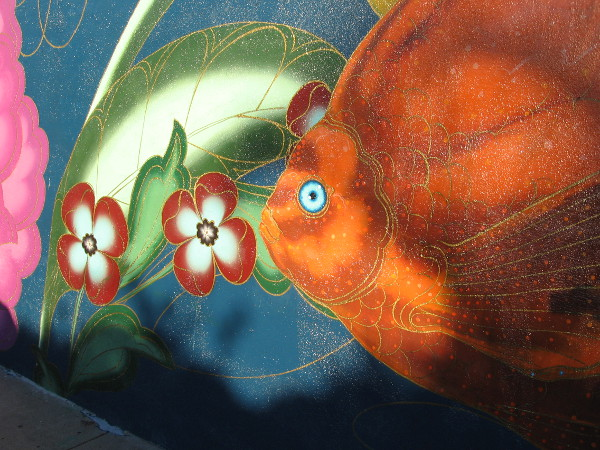 A bright orange fish swims past jewel-like flowers.