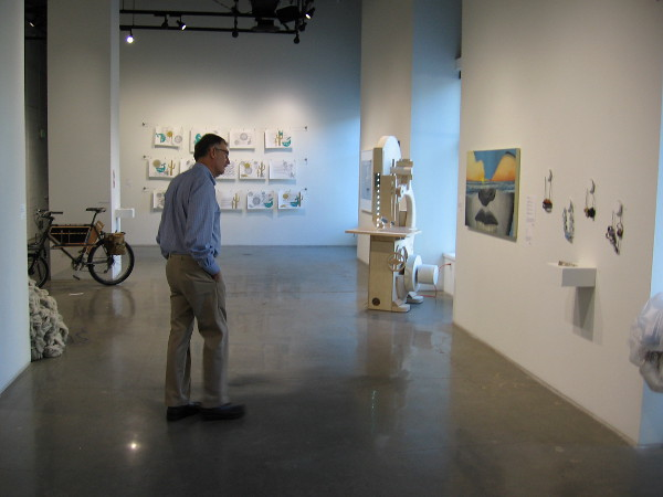Visitor to the gallery checks out thought-provoking artwork.