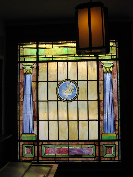 Stained glass shows classical columns and a cross in a crown.