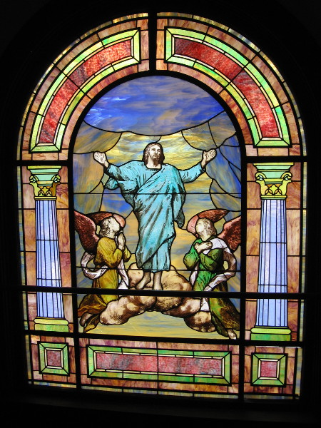 Another vibrant stained glass window portrays a risen Christ in heaven.