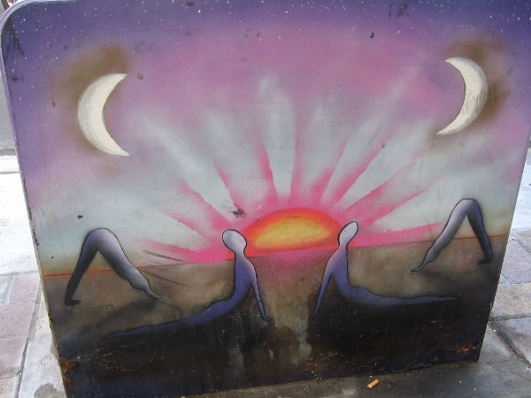 Symmetrically painted figures practice yoga under crescent moons as the sun rises. Cool street art in downtown San Diego.