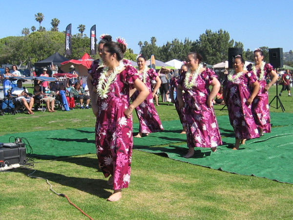 Performers walk off the grassy stage at Crown Point during the San Diego Shaka Fest.