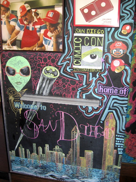 San Diego's Domino's Pizza has a fun wall with lots of pop culture imagery, including an alien, Bat signal, Mario, and the downtown skyline.