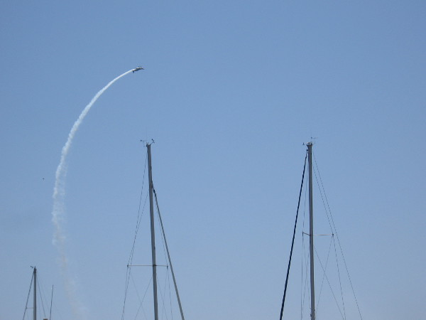 A Red Bull pilot rolls in the sky high above marina masts!