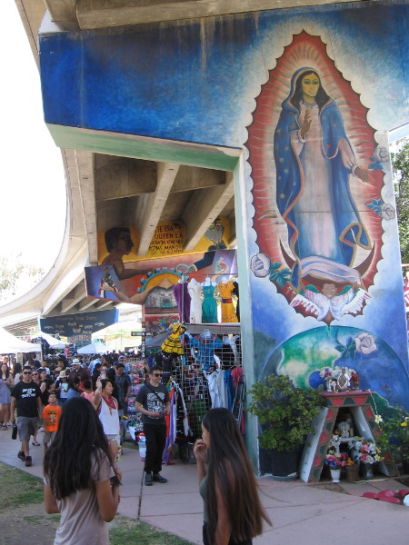 People enjoy Chicano Park Day Celebration among the many expressive murals.