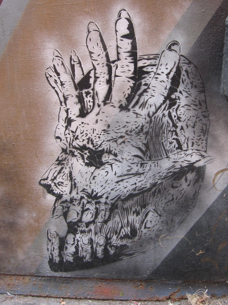 Hands and fingers create an eerie seemingly inhuman skull.