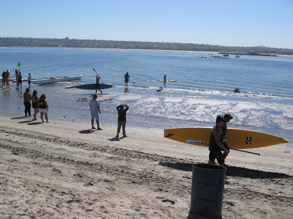 Lots of stand up paddleboards and canoes down on the water of Mission Bay.