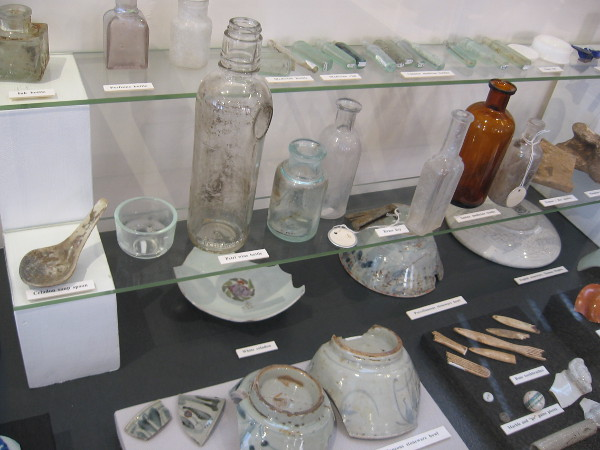Some of many artifacts recovered include glass bottles, ceramic bowls, utensils.