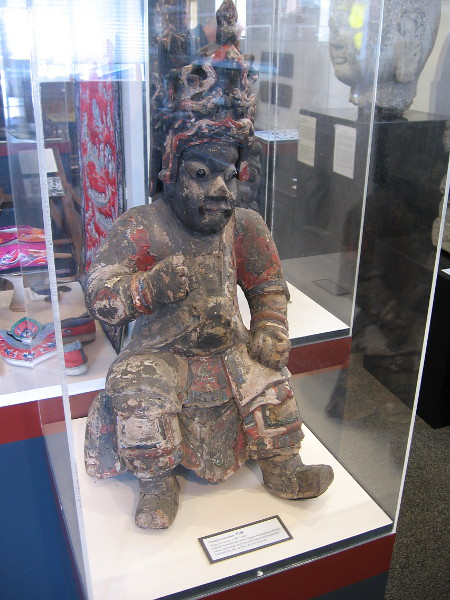 A temple guardian, from Ming Dynasty. The carved wooden idol has a dragon headdress, robes, glass eyes and a real hear beard and mustache.