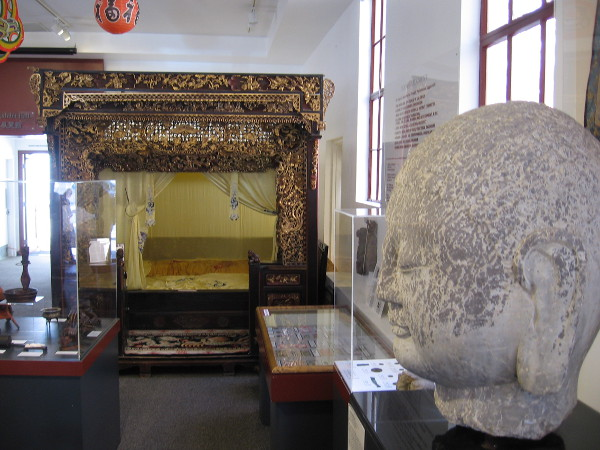 Looking past the Buddha head at a fantastic, ornate alcove bed.