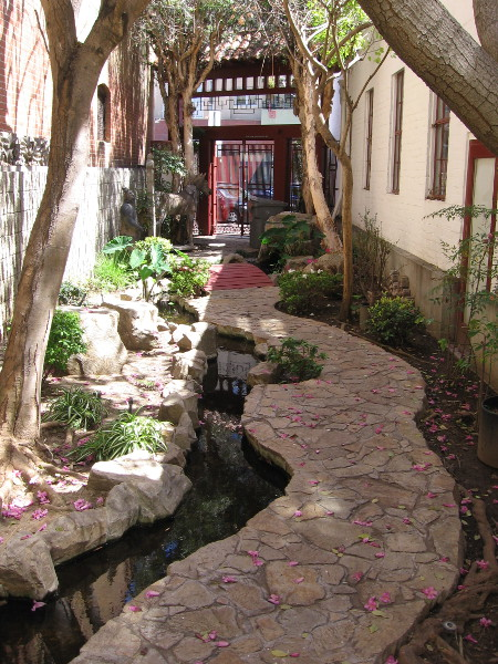 A tranquil path runs beside water along the north side of the San Diego Chinese Historical Museum.