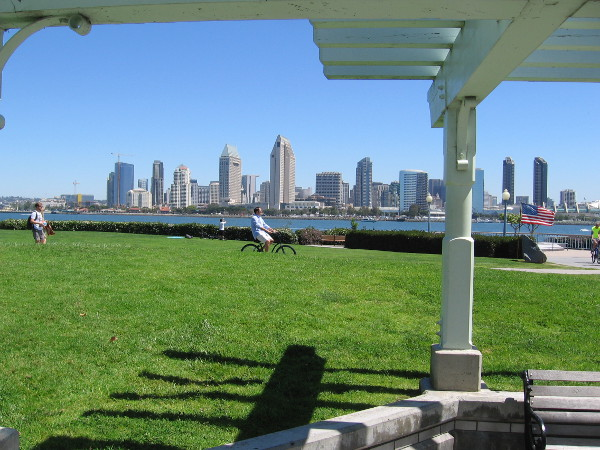 Gazing from a sheltered area with benches across green grass. The skyline of downtown San Diego rises in the background.