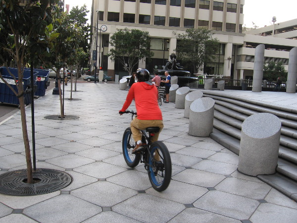Someone rides a bicycle along B Street during San Diego's Bike to Work Day.
