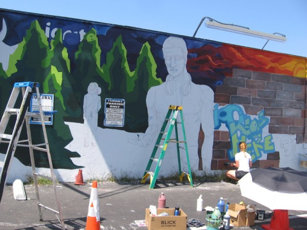 Ion Theatre artist Kate Schott paints a cool mural on a wall in Hillcrest.