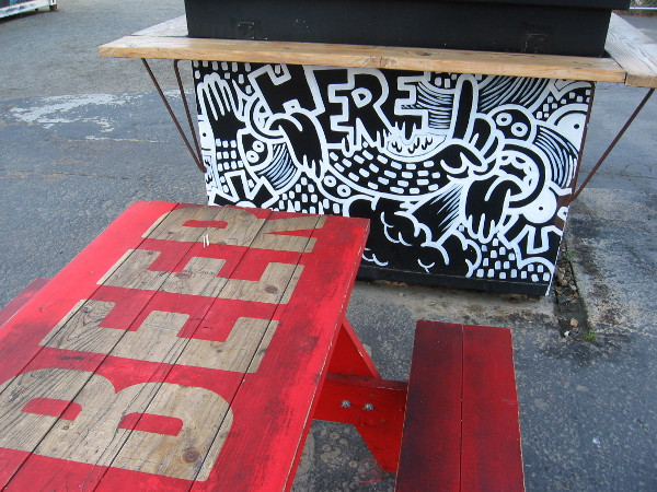 Picnic table in the Quartyard reads beer, next to a planter with fun artwork.