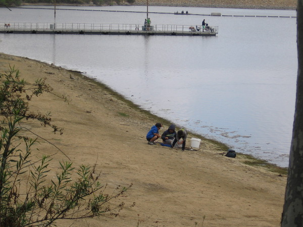 These kids who are fishing huddle together to check out something on the lake's shore.