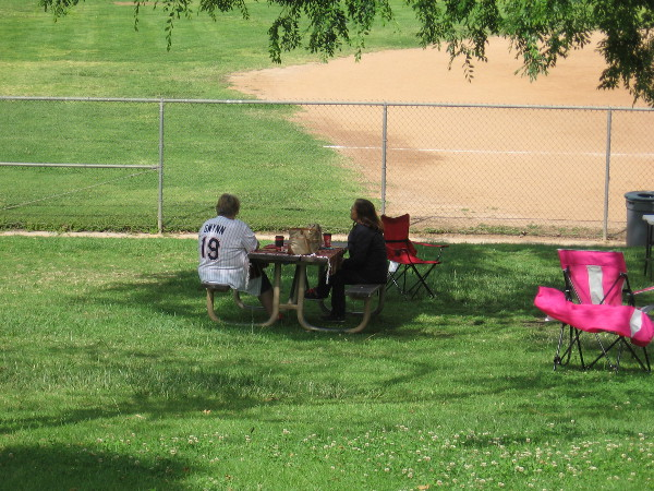 Someone in a Gwynn San Diego Padres jersey sits by the softball field at Lake Poway, not far from the statue.