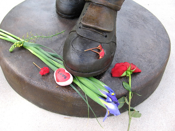 Flowers and a heart with the word LOVE at Tony's feet.