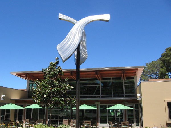 A shining, kinetic sculpture by the library turns in the breeze.