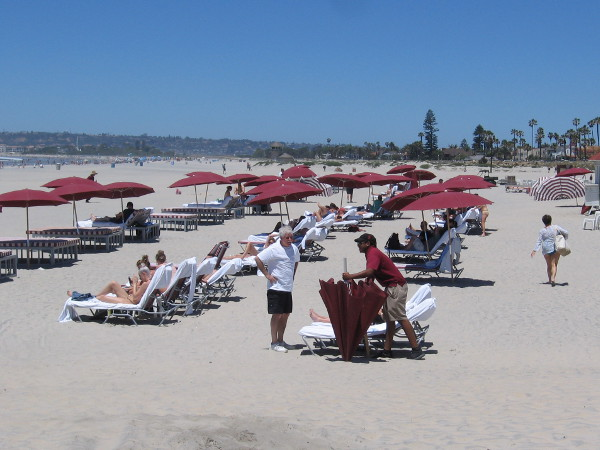 Hotel guests and visitors enjoy the San Diego sunshine on a broad white beach.