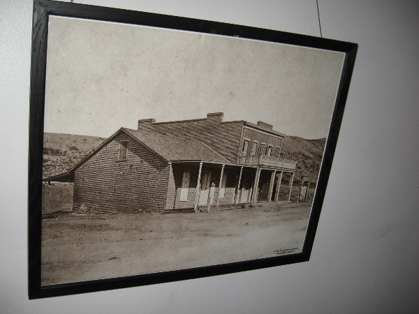 Photograph on the courtroom's back wall shows the Whaley House on the outskirts of tiny San Diego. It stands alone in barren place. It was built on a hanging ground not far from old El Campo Santo Cemetery.