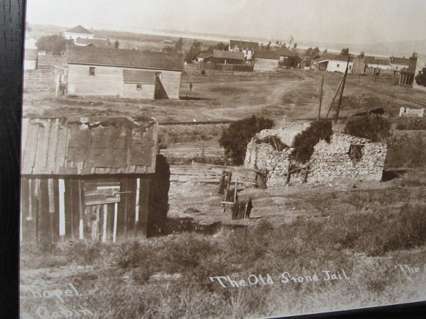 Another photo in the courtroom shows San Diego's old stone jail in a crumbling state. It stands next to the chapel cabin and the old graveyard.