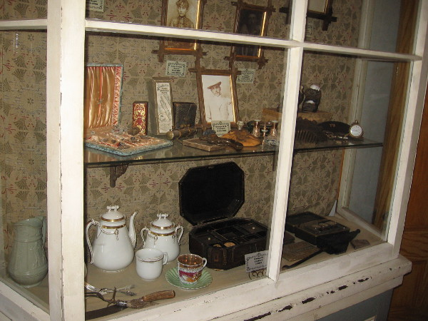 A nearby display case contains items belonging to various members of the Whaley family, including engraved silverware and china.