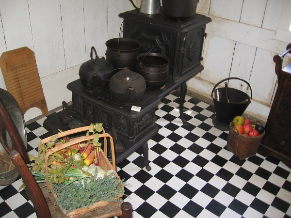 The tour proceeds to the reconstructed kitchen, which seeks to replicate the original board and batten structure. The checked floor is typical of the era.