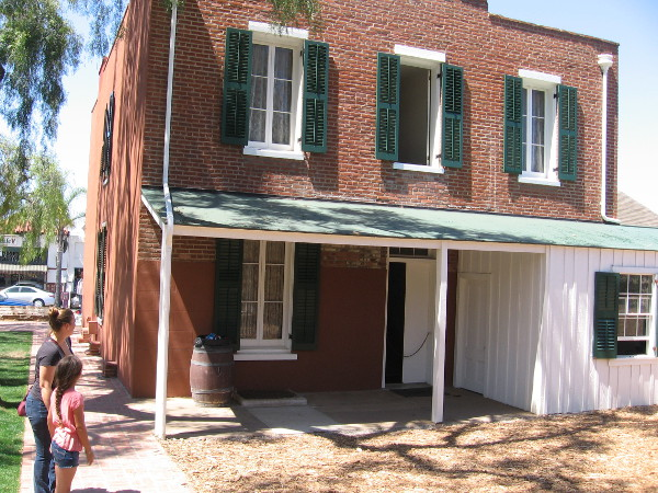 Photo of rear of Whaley House. The white detached room is the kitchen. In case of fire, the burning walls of the kitchen would be pulled away from the main building by horse.