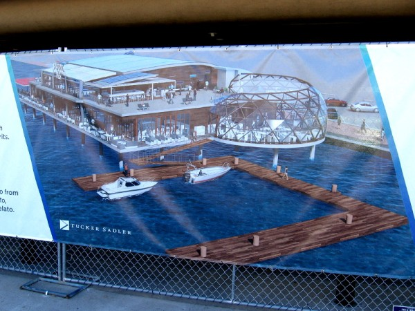 Graphic on a banner on the fence surrounding the old, closed Anthony's Fish Grotto. A new waterside dining experience is coming called Portside Pier.