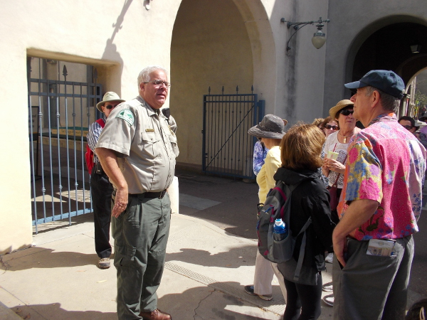 Ranger Kim relates the history of Balboa Park to a tour group. They stand by the original Administration Building, which was the first building constructed for the 1915 Panama-California Exposition.