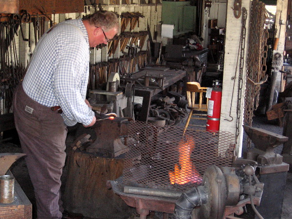 A blacksmith shapes red hot iron at a forge in San Diego's historic Old Town.