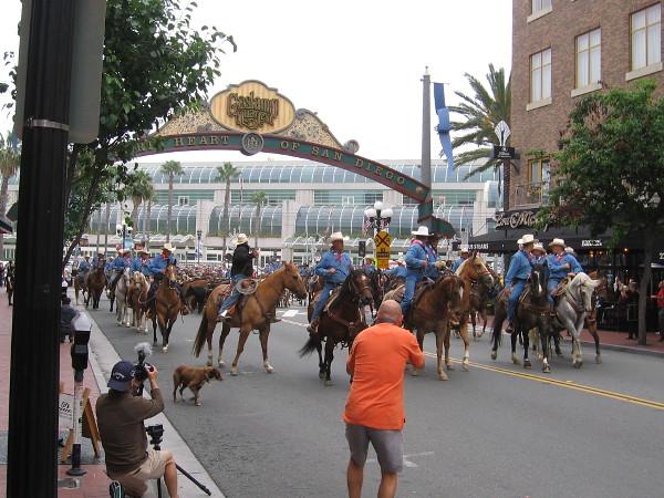 Cowboys ride under the Gaslamp Quarter landmark sign.