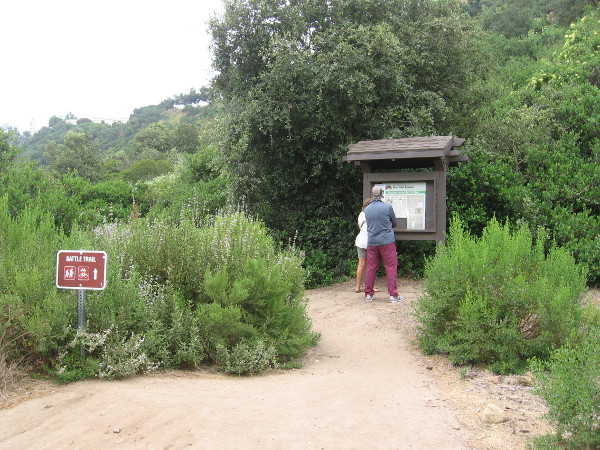 Hikers read the sign at the Battle Trail trailhead.