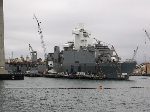 Navy ships are undergoing repairs and modernization. The white plastic wrap prevents paint particles from entering the environment.