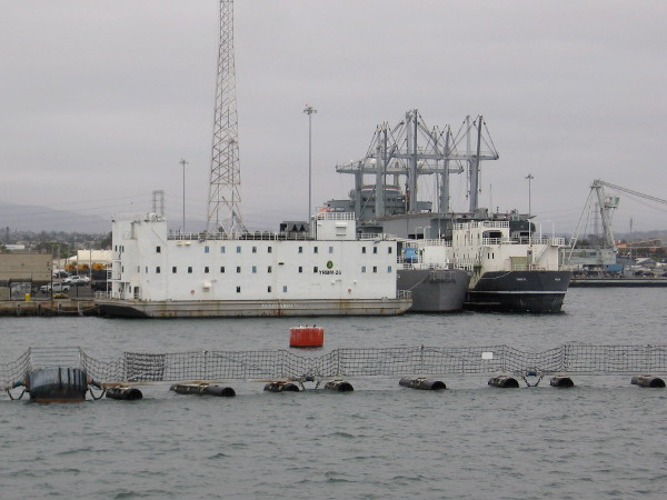 The unusual white vessel is a barracks barge--where a crew lives while their Navy ship is undergoing major repairs.