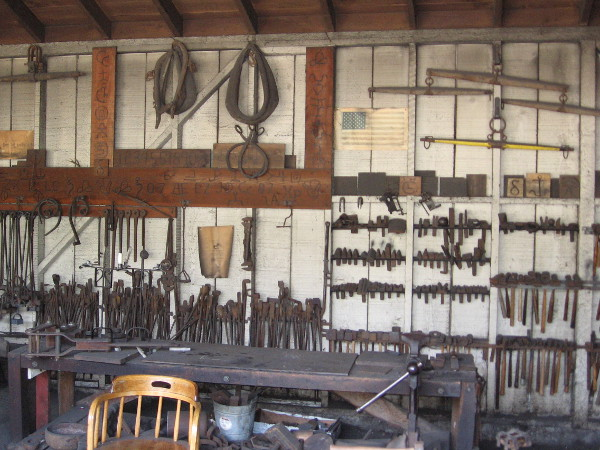 Hammers, bars, wrenches and various blacksmithing tools hang from the rear wall, in addition to harnesses and other items one might find in a livery stable.