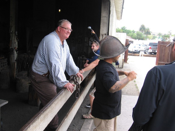 Old Town visitor tries on a Spanish conquistador helmet made in the Blacksmith Shop.